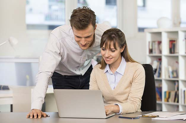Colleagues look at laptop screen together