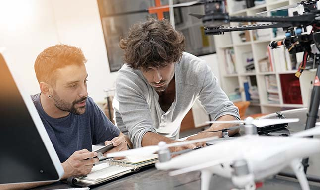 Two men brainstorming in lab with robots on desk