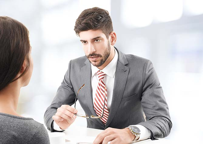 Businessman talking to woman across desk from him