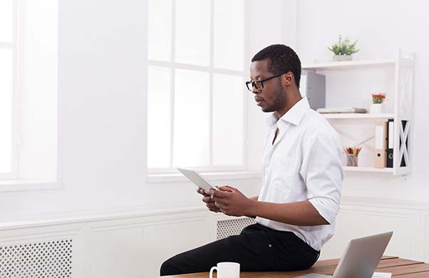 Man in glasses leaning against desk and looking down at tablet in hand