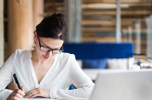 Woman writing in notebook at desk
