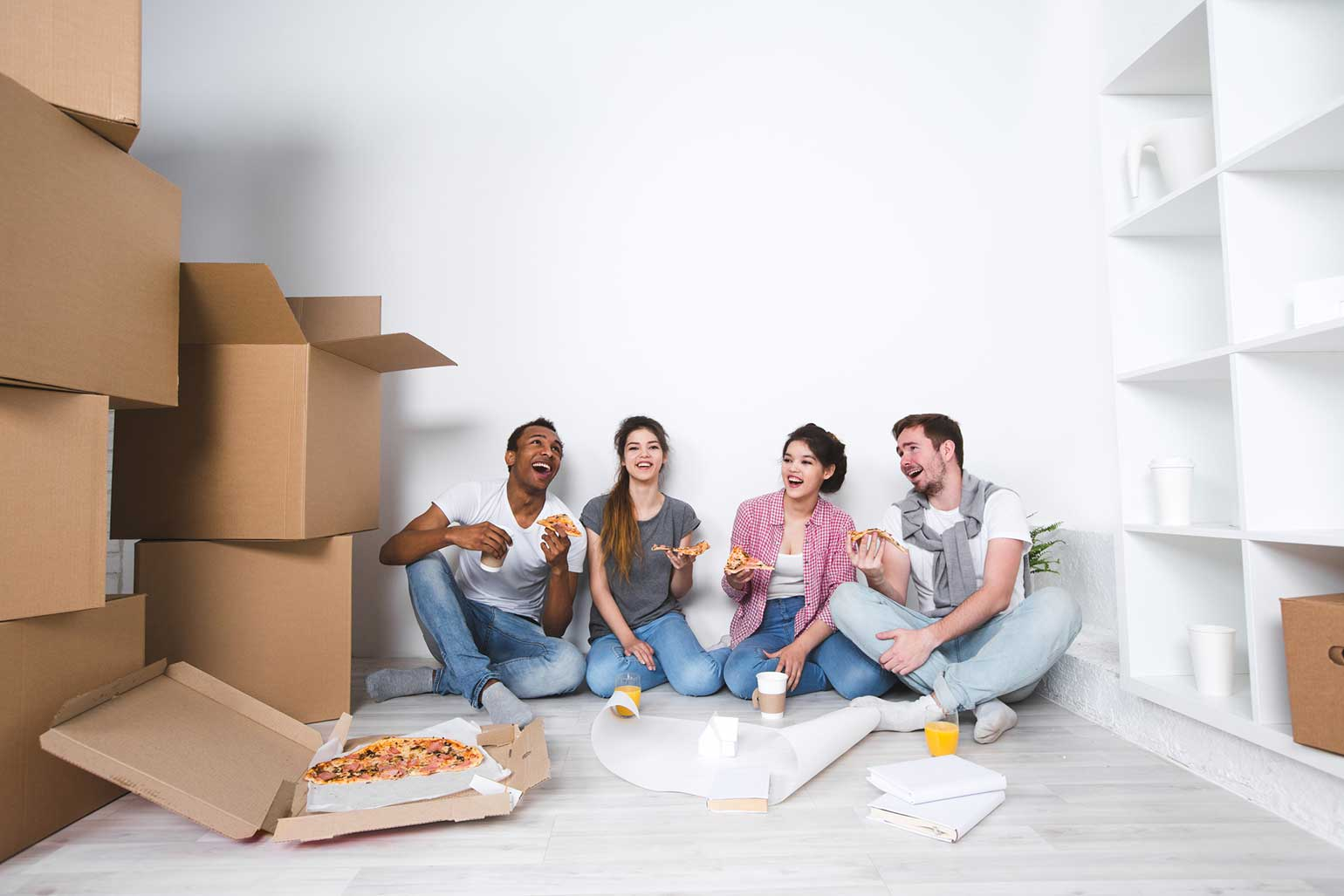 Happy first time home buyers and their 2 friends eating pizza on the floor after unpacking moving boxes.
