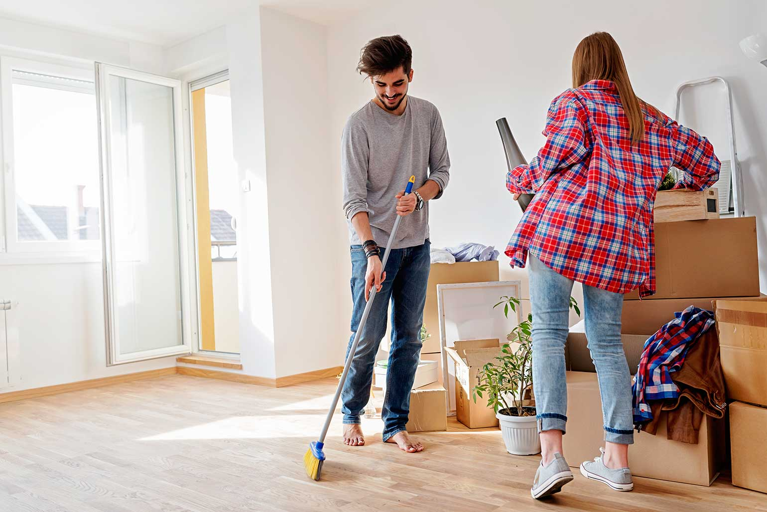 First time home buying couple cleaning their new condo before unpacking their moving boxes
