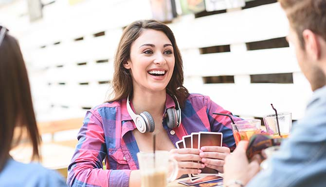 Woman in flannel playing card game with friends while laughing and wearing headphones around her neck