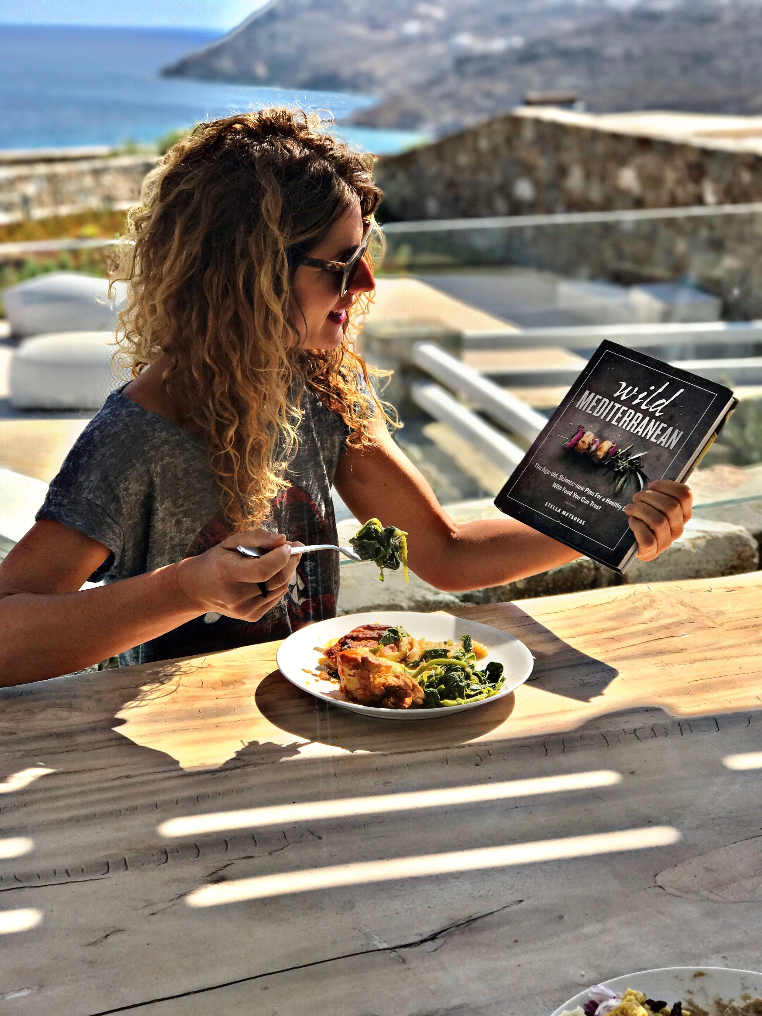 Stella metsovas eating lunch and enjoying her latest book while stella photographed with her book lastest book while visiting mykonos 2c greece.  credit   stella metsovas.