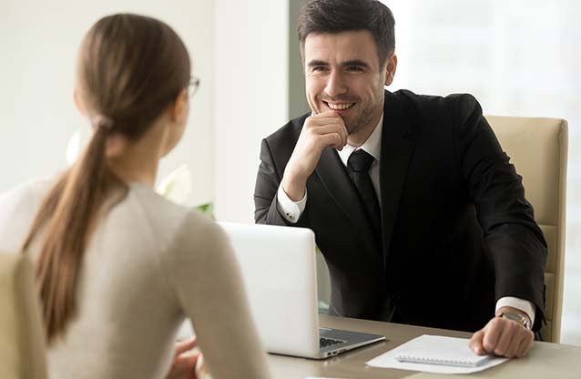 Businessman smiling at woman across desk
