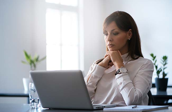 Woman looking down at laptop