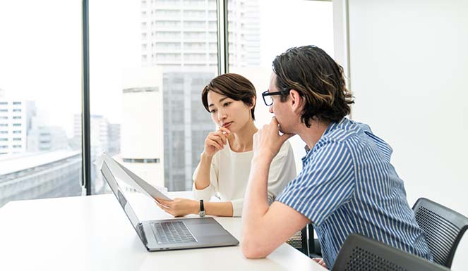 Businessman and businesswoman in office overlooking city looking at document over computer