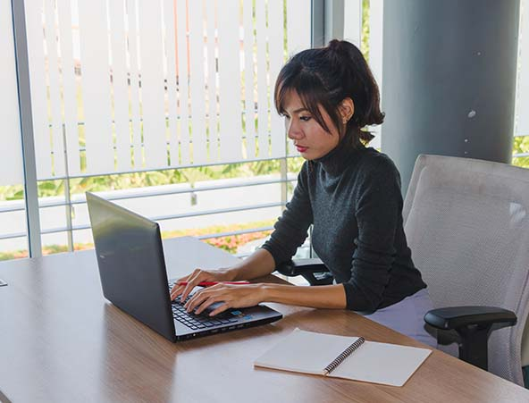 Woman typing on computer in office