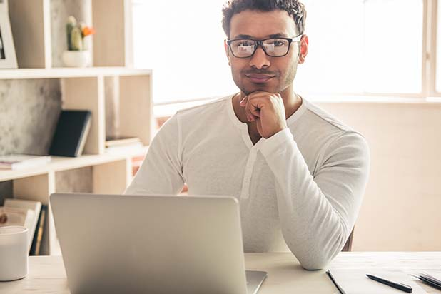 Man smiling with head resting on hand in front of laptop