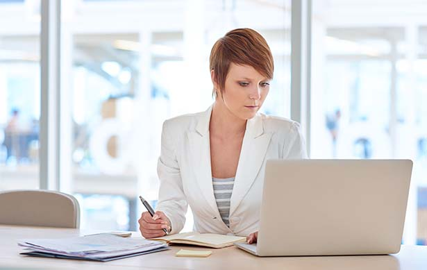 Woman with short hair looking at computer and writing on paper