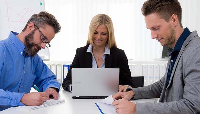 Businesswoman types at laptop with two businessmen on either side of her writing in notebooks