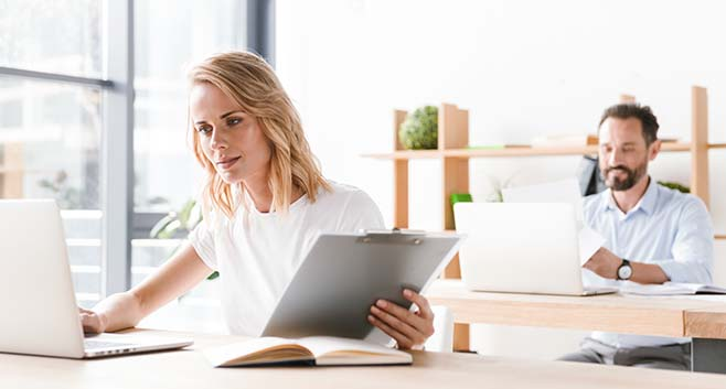 Woman in shared office typing on laptop and holding clipboard