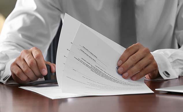Man in suit shuffling through documents