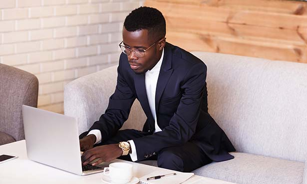 Man in dapper suit leaning over on couch typing on laptop on white table with coffee cup on it while wearing gold watch