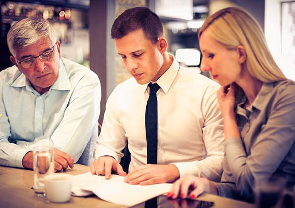 Man in suit looking at documents with more casually dressed people on either side of him