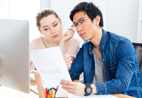 Man and woman looking at documents at desk