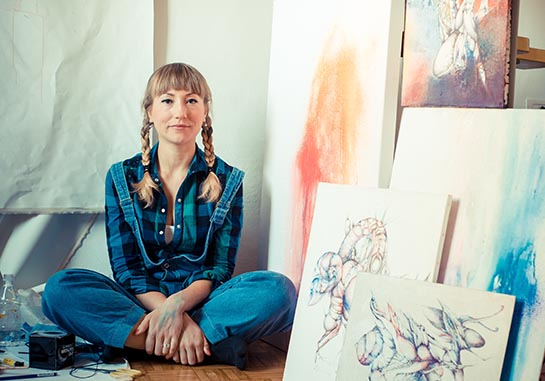 Woman with braids and bangs sitting cross-legged in studio surrounded by paintings