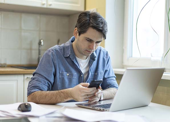 Man sitting at desk looking at phone in front of laptop