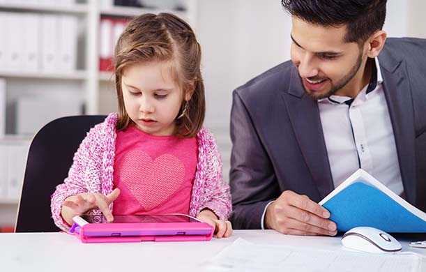 Man in suit smiling and sitting next to toddler playing game on pink tablet