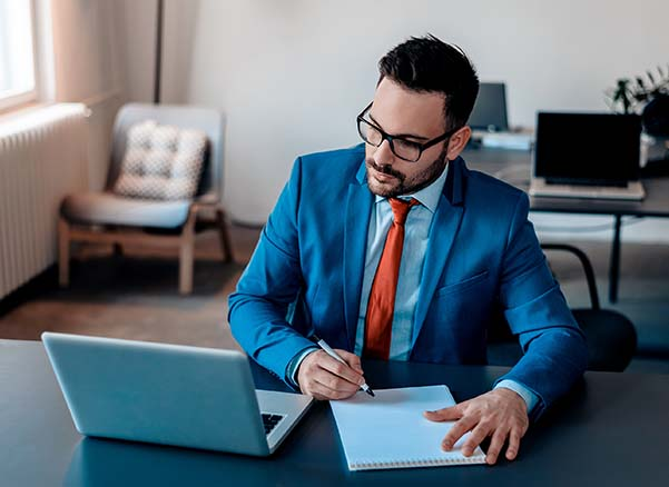 Man in blue suit looking at laptop while writing in notebook.