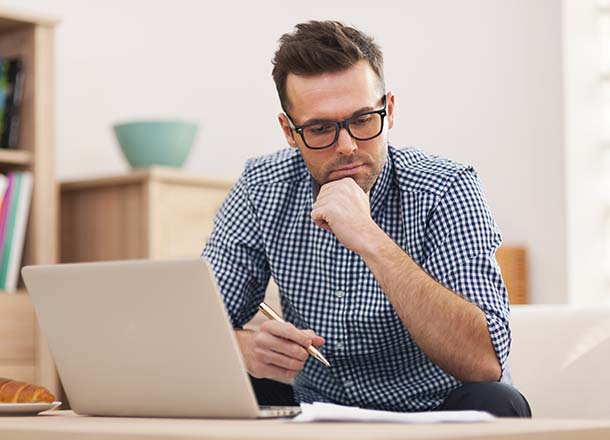Man sitting in front of laptop at desk