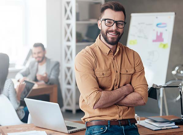 Hipster man leaning against wooden desk and smiling while crossing arms