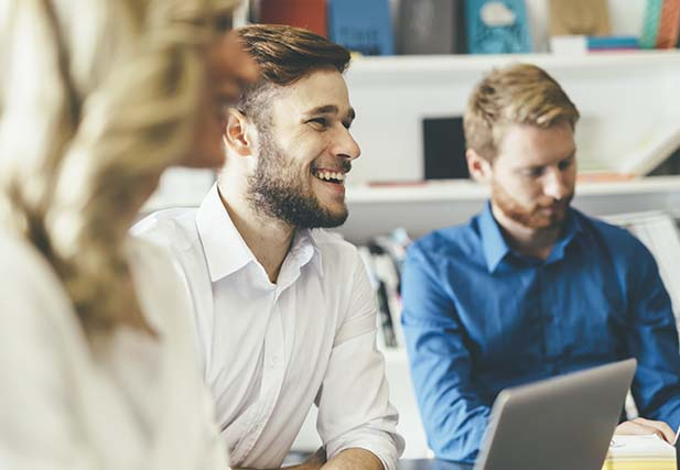 Man surrounded by colleagues laughing while sitting in front of laptop