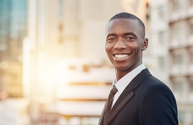 Man in suit smiling with skyscrapers in background