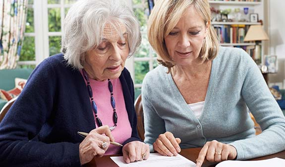 Middle aged woman looking over documents with elderly mother in home