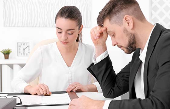 Businesswoman and businessman look over documents
