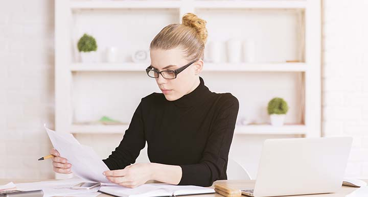 Woman in black turtleneck looking down at documents and holding pens in minimalist office space