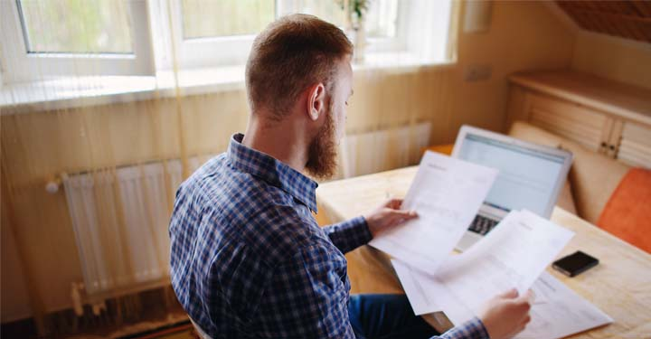 Man in plaid shirt sitting at a table in his house holding paperwork
