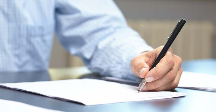 Man in blue button up shirt going over document with pen
