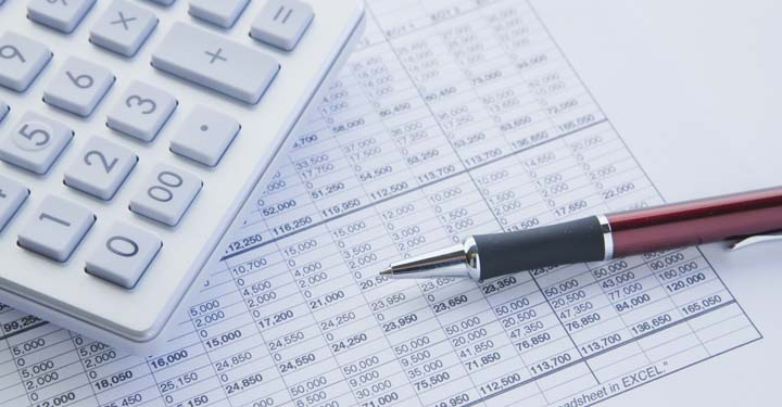 Calculator, pen, and financial documents