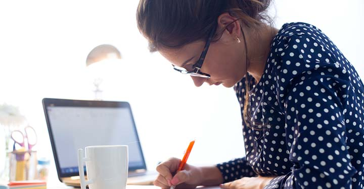 Woman holding pen and writing at a table with a cup of coffee and her laptop next to her