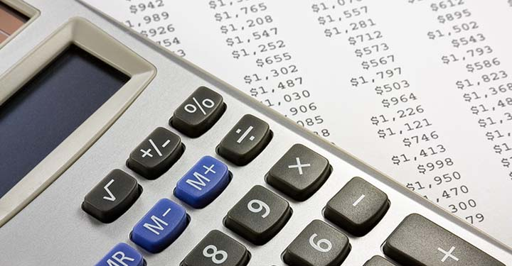 Calculator resting on piece of paper containing a list of amounts of money