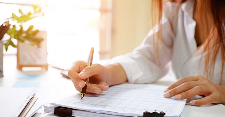 Woman at desk with fountain pen looking over papers