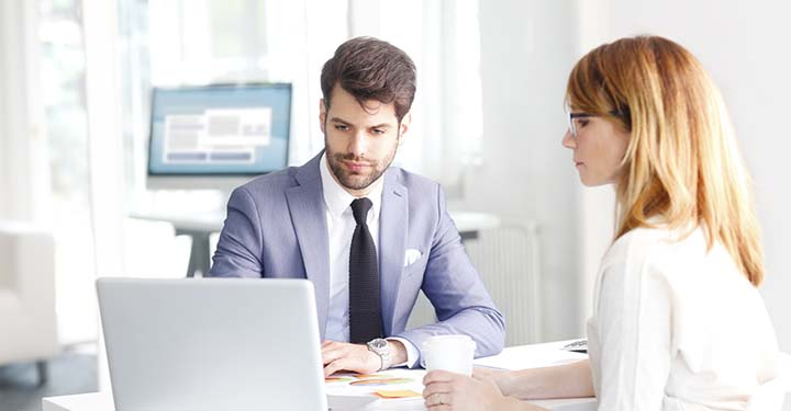Businessman in suit and silver watch scrolling on laptop next to woman in white cardigan holding coffee cup on white desk in office