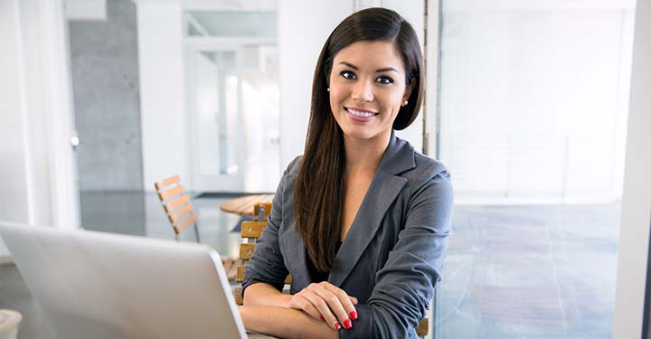 Woman with crossed arms smiling behind her open laptop