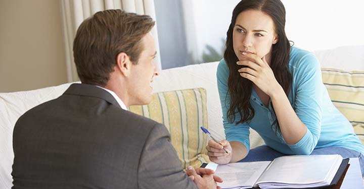 Woman in blue shirt with ballpoint pen hovering over documents looks at talking man in suit