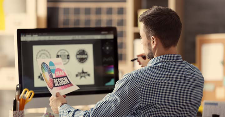 """Graphic designer looking at paper that says """"design"""" on it and logos on his computer screen"""