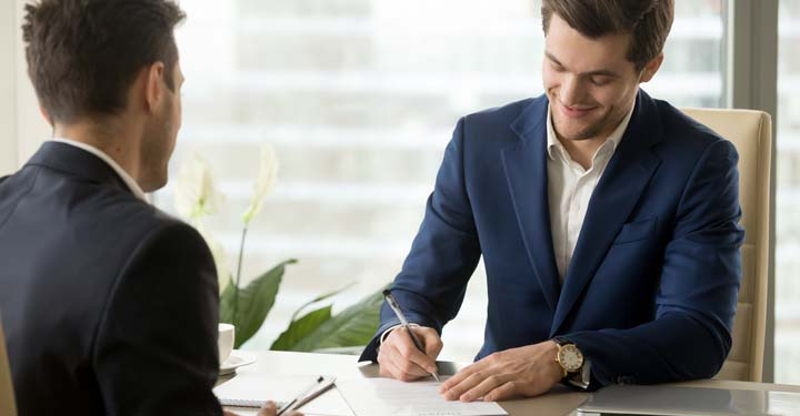 Businessman signing documents as a coworker watches from across the desk