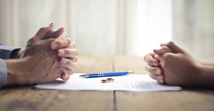 Men and women's hands on opposite sides of paper with wedding rings and pen resting on it