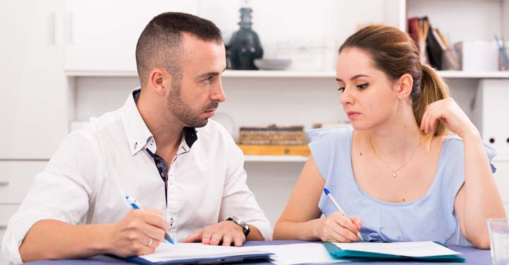 Man and woman sadly looking at each other while they hold ballpoint pens over forms