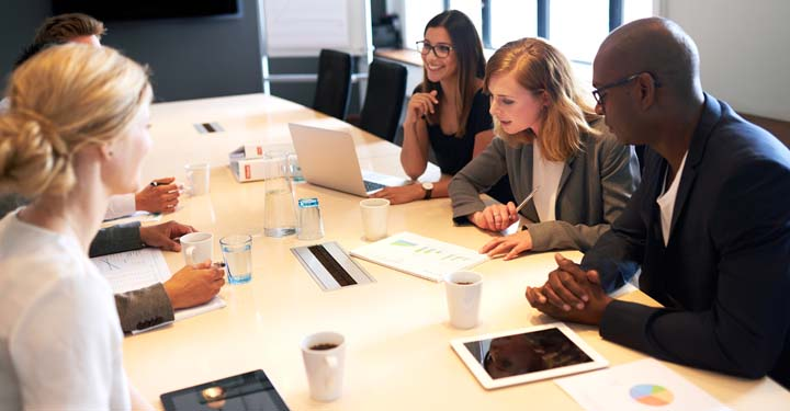 Businesspeople discussing at conference table with coffee, water, laptops, and iPads