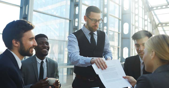 Businessman in group of businesspeople hands businesswoman paper