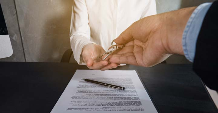 Hands passing house keys from one person to another.  Paperwork and a pen sit on the table