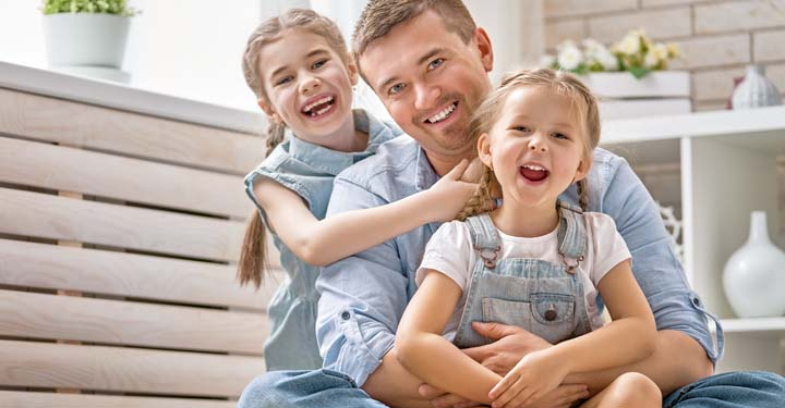 Smiling dad sitting with his two laughing children in matching light wash denim in living room