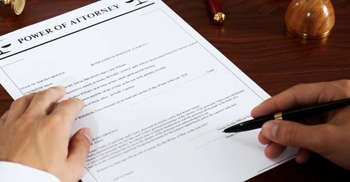 Man signing power of attorney document with ballpoint pen